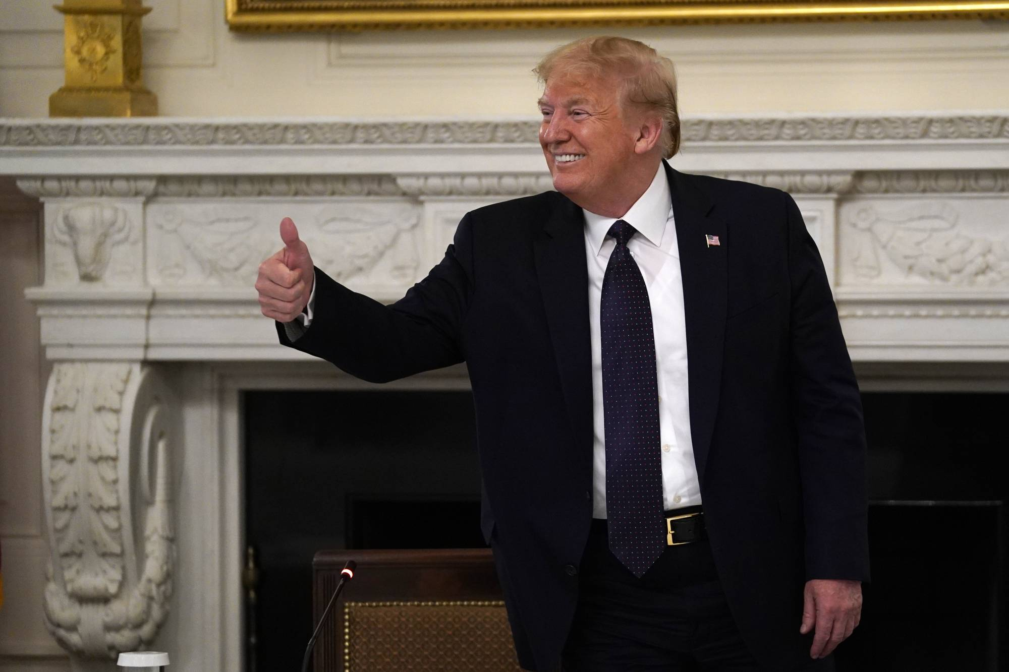 U.S. President Donald Trump gestures as he leaves a meeting with restaurant industry executives about the coronavirus response, in the State Dining Room of the White House on Monday.  | AP