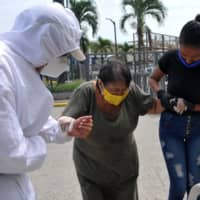 A health worker helps a woman as she enters a field hospital for COVID-19 patients at the Conventions Center in Guayaquil, Ecuador, on April 30. | AFP-JIJI