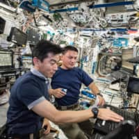 JAXA astronaut Kimiya Yui and NASA astronaut Kjell Lindgren work on the International Space Station in August 2015. While not all the experiences of astronauts are necessarily applicable to stay-at-home life on Earth, the challenges are essentially the same. | COURTESY OF NASA