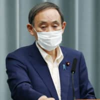 Chief Cabinet Secretary Yoshihide Suga talks about the Diplomatic Bluebook annual foreign policy report at the Prime Minister's Office in Tokyo on Tuesday. | KYODO