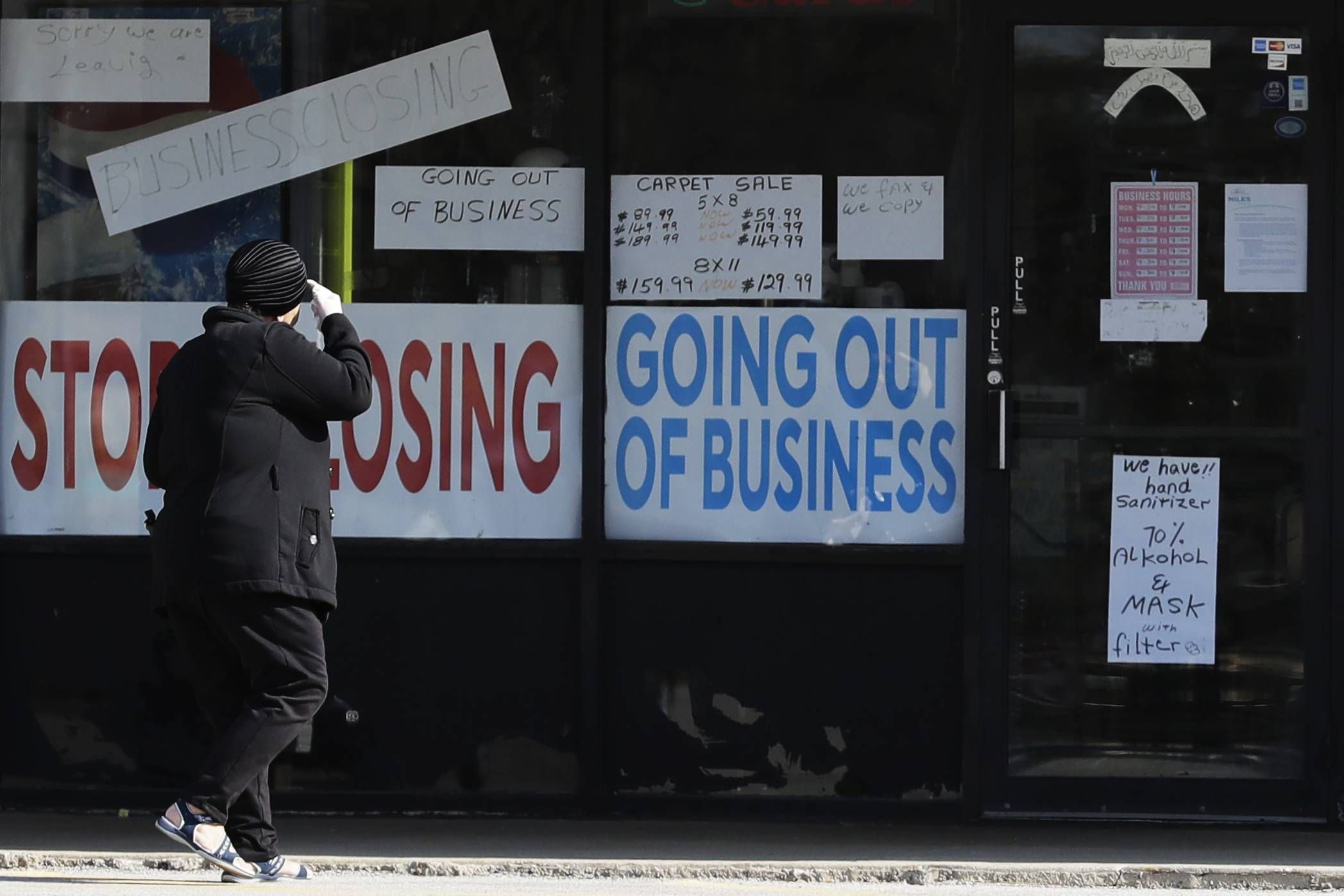 A women looks at signs on a store in Niles, Illinois, on May 13. From leisure to hospitality to retail, entire industries in which women make up a greater share of the workforce have been brought to a halt by the pandemic as more than 20 million Americans lost their jobs in April alone. | AP