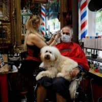 A hairdresser wearing a protective mask cuts the hair of a man at a barber shop, as Miami-Dade County eases some of the lockdown measures put in place during the coronavirus disease outbreak, in Miami on Monday. | REUTERS
