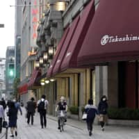 Pedestrians walk past a reopened Takashimaya Co. department store in the Nihonbashi district of Tokyo on Monday. | BLOOMBERG