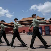 People's Liberation Army soldiers march past the entrance to the Forbidden City in Beijing on Monday. The annual meeting of the National People's Congress, China's rubber-stamp legislature, opens on Friday after a two-month delay due to the coronavirus pandemic. | AFP-JIJI