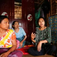 Zarchi Liwn, one of hundreds of thousands of garment workers across Asia who have been laid off, talks to reporters in her hostel in an industrial zone on the outskirts of Yangon, Myanmar, last month.  | REUTERS