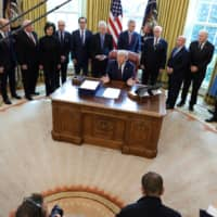 Extending a lifeline: U.S. President Donald Trump signs the $2.2 trillion H.R. 748 CARES Act coronavirus aid package bill in the Oval Office of the White House on March 27. | REUTERS