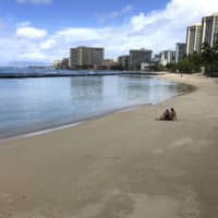 A couple sits on an empty section of Waikiki Beach in Honolulu on March 28. Hawaii law enforcement authorities are cracking down on rogue tourists who are visiting beaches, jetskiing, shopping and generally flouting strict requirements that they quarantine for 14 days after arriving. | AP