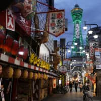 Tsutenkaku Tower in Osaka is lit up in green on Tuesday to symbolize that the prefecture has met the criteria to lift its business closure requests. | KYODO
