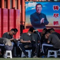 Chinese soldiers clean their boots next to a poster with a picture of Chinese President Xi Jinping at the entrance to Beijing's Forbidden City on Tuesday. | AFP-JIJI