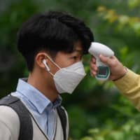 A student's temperature is checked upon arrival at Kyungbock High School in Seoul on Wednesday.  | AFP-JIJI