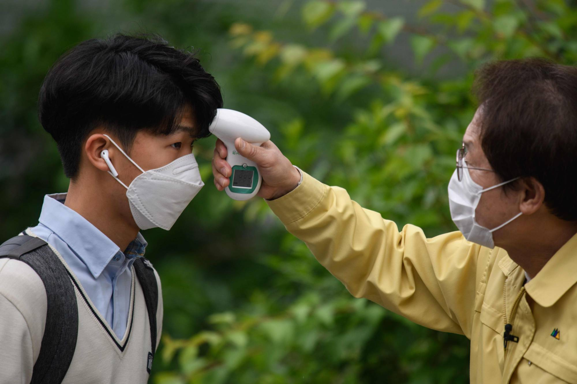 A student's temperature is checked upon arrival at Kyungbock High School in Seoul on Wednesday.    AFP-JIJI