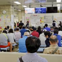 The Shinagawa Ward office in Tokyo is crowded on May 11 with people going through procedures to obtain a My Number card, necessary for online application to receive a ¥100,000 cash handout. | KYODO