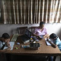 A mother helps her children with online homework in Caracas earlier this month.   AP