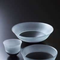 Patina: From photo top, this deep dish (18.5 x 7 centimeters), sake cup (7.5 x 6 centimeters) and bowl (13 x 6 centimeters) with black base and silk-thread pattern, ¥50,000 each, are by Masao Adachi. Applying an original technique, Adachi mixes a special blend of materials to produce the black glass, which he builds up in multiple layers while firing each in turn. The result is a rare vessel that changes its appearance over time, acquiring more luster the more it is used. |
