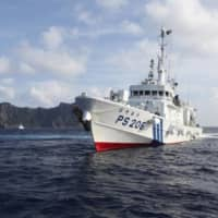 A Japan Coast Guard vessel sails in front of Uotsuri Island, one of the Japanese-administered Senkaku Islands in the East China Sea, in August 2013.  | REUTERS