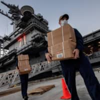 U.S. Navy sailors assigned to the aircraft carrier USS Theodore Roosevelt move meals ready to eat (MREs) for sailors who have tested negative for the new coronavirus and are asymptomatic while quarantined at local hotels in an effort to implement social distancing at the naval base on the Pacific island of Guam on April 7. | U.S. NAVY / VIA REUTERS