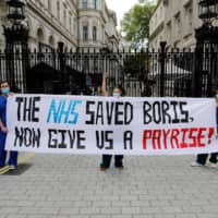 Nurses who work at central London hospitals hold a protest outside Downing Street in central London on May 13 to call for improved conditions and pay. Since 2015, the U.K.'s National Health Service has endured massive budget cuts. | AFP-JIJI