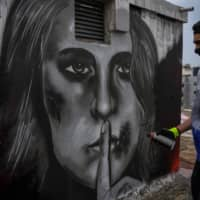 Sixteen-year-old Greek graffiti artist S.F. paints on the roof of a building in Athens last month. The image depicts a woman with injuries on her face and her finger over her lips, inspired by the increase in cases of domestic violence amid worldwide lockdowns. | AFP-JIJI