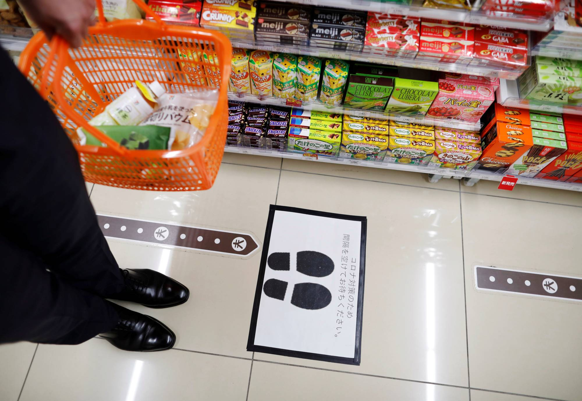 A social distancing marker in front of a checkout counter at a Seven-Eleven convenience store in Tokyo | REUTERS