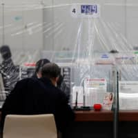 A bank teller wearing a protective face mask works at a counter where a plastic curtain is installed in order to protect against the coronavirus at the Higashinakano branch of MUFG Bank in Tokyo last month. | REUTERS
