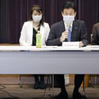 Yasutoshi Nishimura (right), the Cabinet minister in charge of dealing with the coronavirus pandemic, addresses a government panel meeting on issues related to the state of emergency on Thursday morning in Tokyo. | KYODO