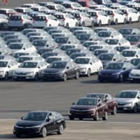 New cars await export at Yokohama port, near Tokyo. | REUTERS