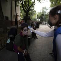A volunteer takes the temperature of a homeless man with his face painted in Mexico City on Wednesday.  | AP