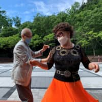 Jeong Nam-poong, 89, and Jang Yoon-hui, 80, dance at a park because their daytime discotheque is closed due to COVID-19, in Seoul on Tuesday. | REUTERS