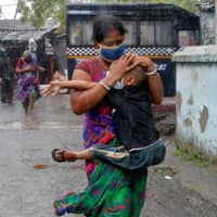A woman carries her son as she tries to protect him from heavy rain while they rush to a safer place, following their evacuation from a slum area before Cyclone Amphan made its landfall, in Kolkata on Wednesday.  | REUTERS