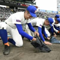 Homare High School (Aichi Prefecture) players scoop up dirt from the field after losing to Aomori Prefecture's Hachinohe Gakuin Kosei High School during the National High School Baseball Championship on Aug. 6, 2019, in Nishinomiya, Hyogo Prefecture. | KYODO