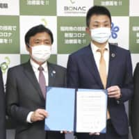 Bonac Corp. CEO Hirotake Hayashi (right) and Fukuoka Gov. Hiroshi Ogawa pose for photos after signing an agreement to work together to develop a drug to treat the novel coronavirus on Monday. | KYODO