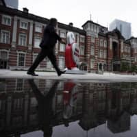 A man wearing a face mask walks in front of Tokyo Station on Wednesday. | AP
