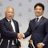 JRFU chairman Kensuke Iwabuchi (right) shakes hands with JRFU president Shigetaka Mori in a news conference on June 29 in Tokyo. | KYODO