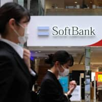 Pedestrians walk past a SoftBank mobile phone store in Tokyo on Monday. | AFP-JIJI