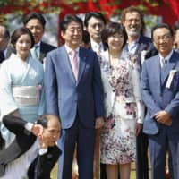 Prime Minister Shinzo Abe, center, poses for photo along with participants of cherry blossom-viewing party in April 2018 in Tokyo. | KYODO