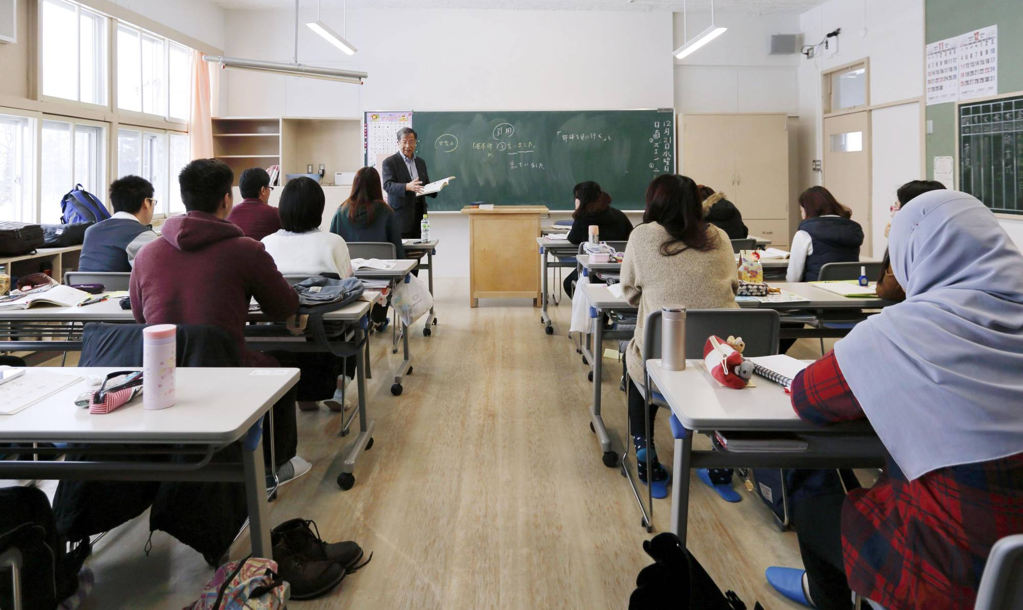 Foreign students attend a class at a Japanese-language school in Hokkaido in December 2016. | KYODO