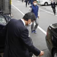 Hiromu Kurokawa walks to a car parked in front of his house in Tokyo on Thursday. | KYODO