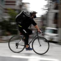 Miyake cycles as he works his part-time job as Uber Eats delivery person in Tokyo during the national state of emergency on May 12. | REUTERS