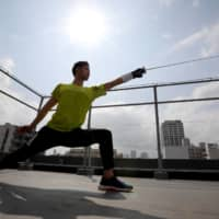 Olympic fencing medalist Ryo Miyake trains at the rooftop of his apartment on May 12. | REUTERS