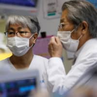 Dr. Shigeki Fujitani (left), the director of the Intensive Care Unit, talks with his predecessor, Dr. Yasuhiko Taira, at the ICU for COVID-19 patients at St. Marianna Medical University Hospital in Kawasaki on May 4. | REUTERS