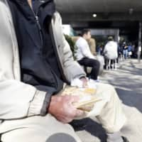 A man sits outside a building in Tokyo's Shinjuku Ward on April 4 after receiving food and consulting from a nonprofit organization working for homeless people and people who lost jobs.  | KYODO
