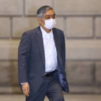 Haruhiko Kuroda, governor of the Bank of Japan, wears a protective mask as he arrives at the central bank's headquarters in Tokyo on Friday. | BLOOMBERG