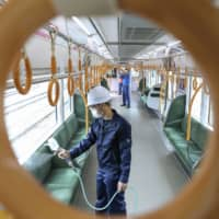 Workers disinfect West Japan Railway Co. trains in the city of Osaka on Friday, a day after the state of emergency was lifted for the prefecture. | KYODO