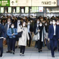 Commuters pass through Tokyo's Shinagawa Station during rush hour on Thursday. Collective actions such as the mass wearing of face masks may help account for Japan's relatively low number of COVID-19 cases despite the lack of a strict lockdown. | KYODO