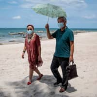Tourists walk along Hua Hin beach in Thailand on Tuesday. Thailand's economy is expected to shrink more than 6 percent this year as the coronavirus outbreak shatters the country's crucial tourism industry, with all flights into the country banned until the end of June. | AFP-JIJI
