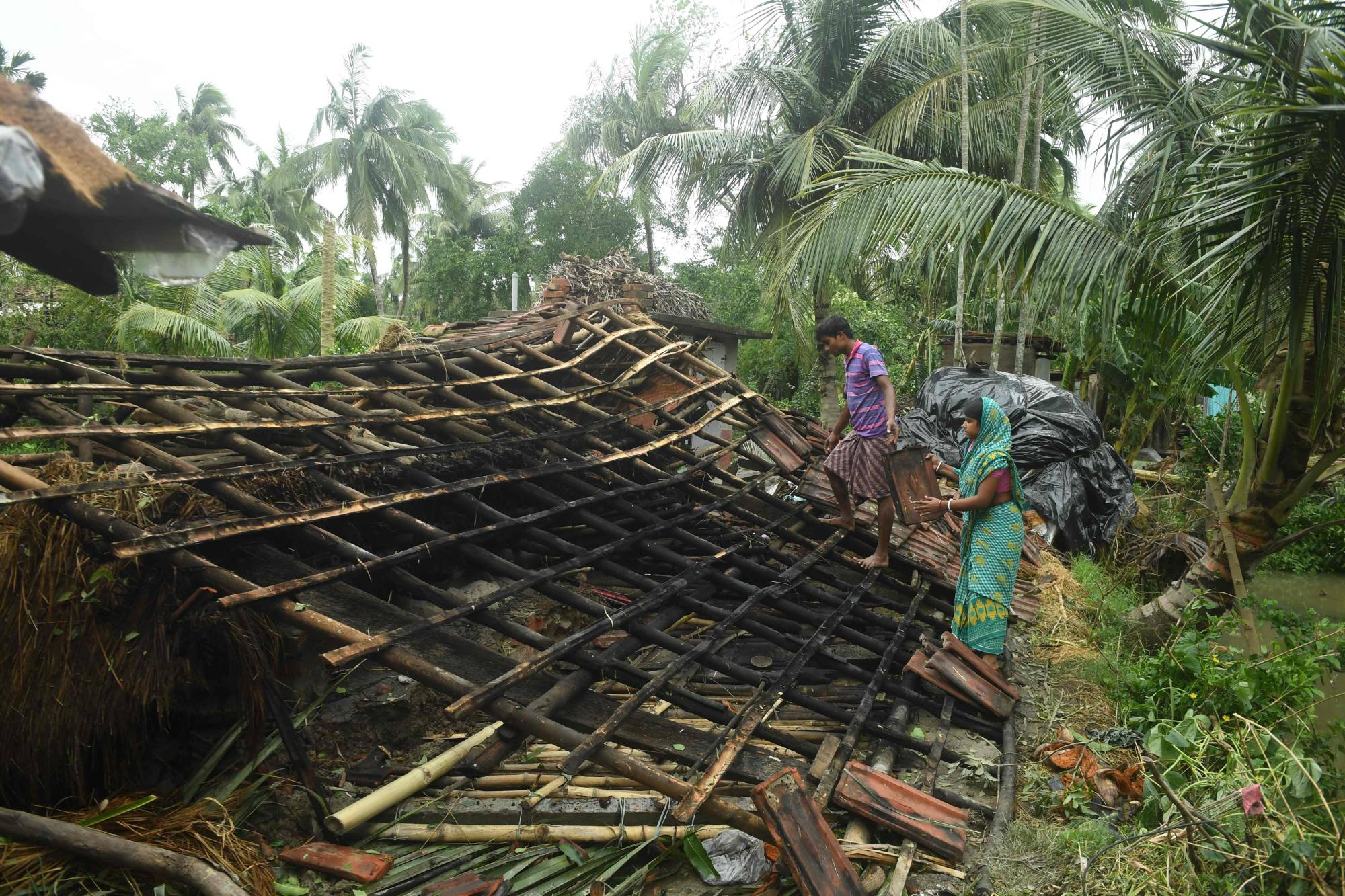 Residents repair the damaged roof of their house following the landfall of Cyclone Amphan in the Khejuri area of Midnapore, West Bengal, India, on Thursday. | AFP-JIJI