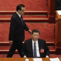 Chinese Premier Li Keqiang walks past President Xi Jinping during the opening session of China's National People's Congress at the Great Hall of the People in Beijing on Friday. | AP