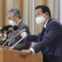 Finance Minister Taro Aso (right) and Bank of Japan Gov. Haruhiko Kuroda hold a news conference on Friday. | KYODO