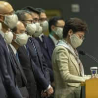 Hong Kong Chief Executive Carrie Lam listens to a question while wearing a protective mask during a news conference in the city Friday. | BLOOMBERG