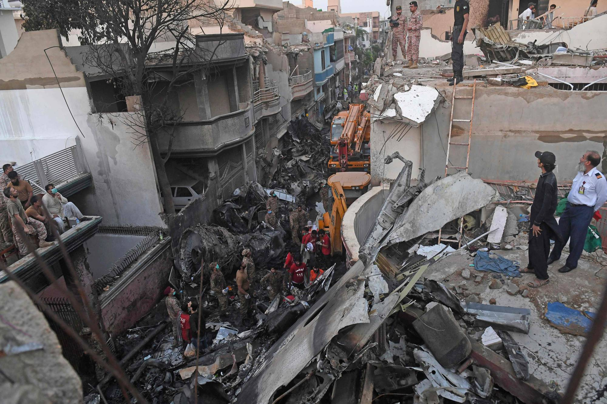 Security personnel search for victims in the wreckage of a Pakistan International Airlines aircraft after it crashed in a residential area of Karachi on Friday. | AFP-JIJI